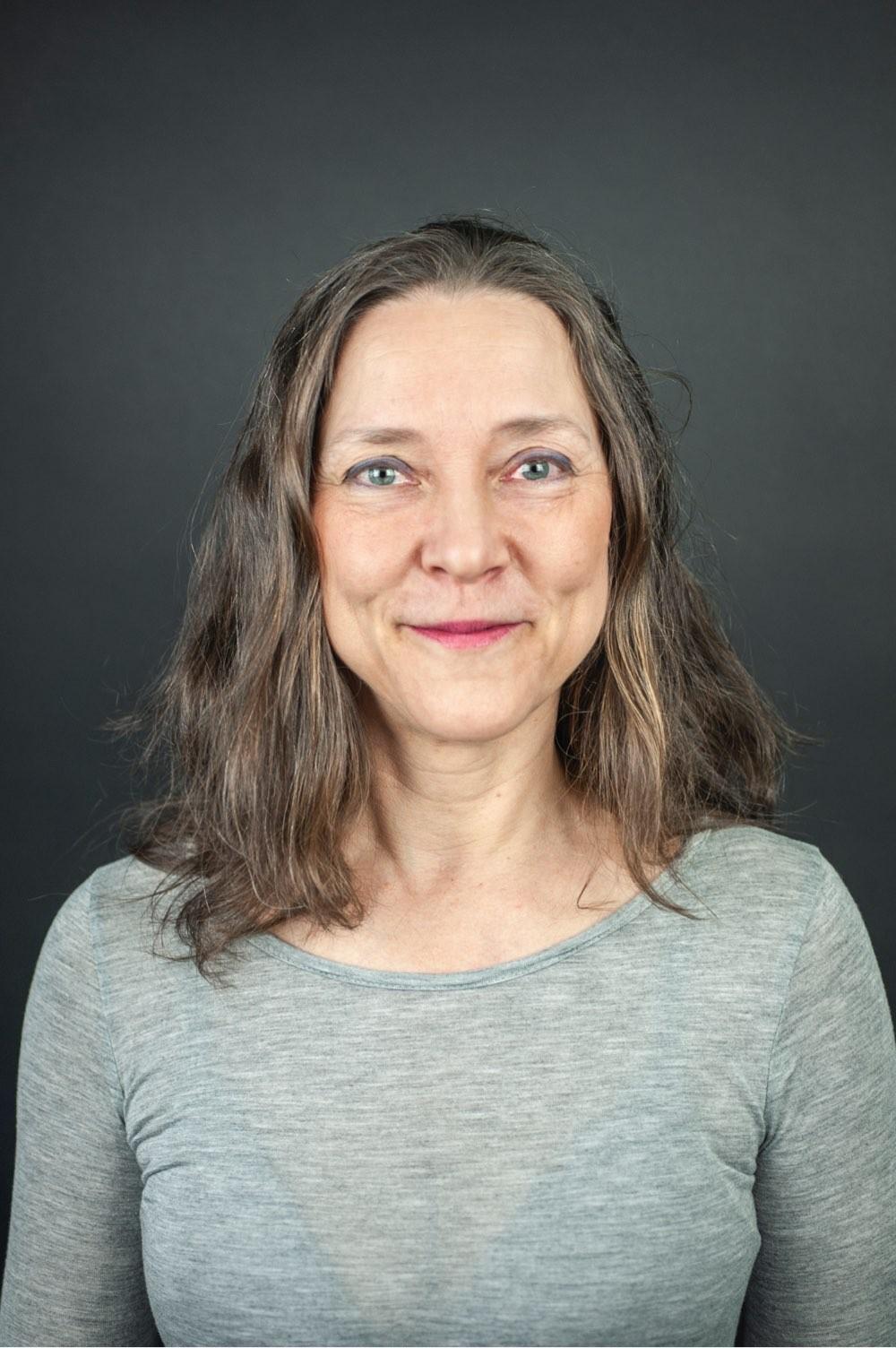 Portrett av Tiina Suhonen - grå bakgrunn
