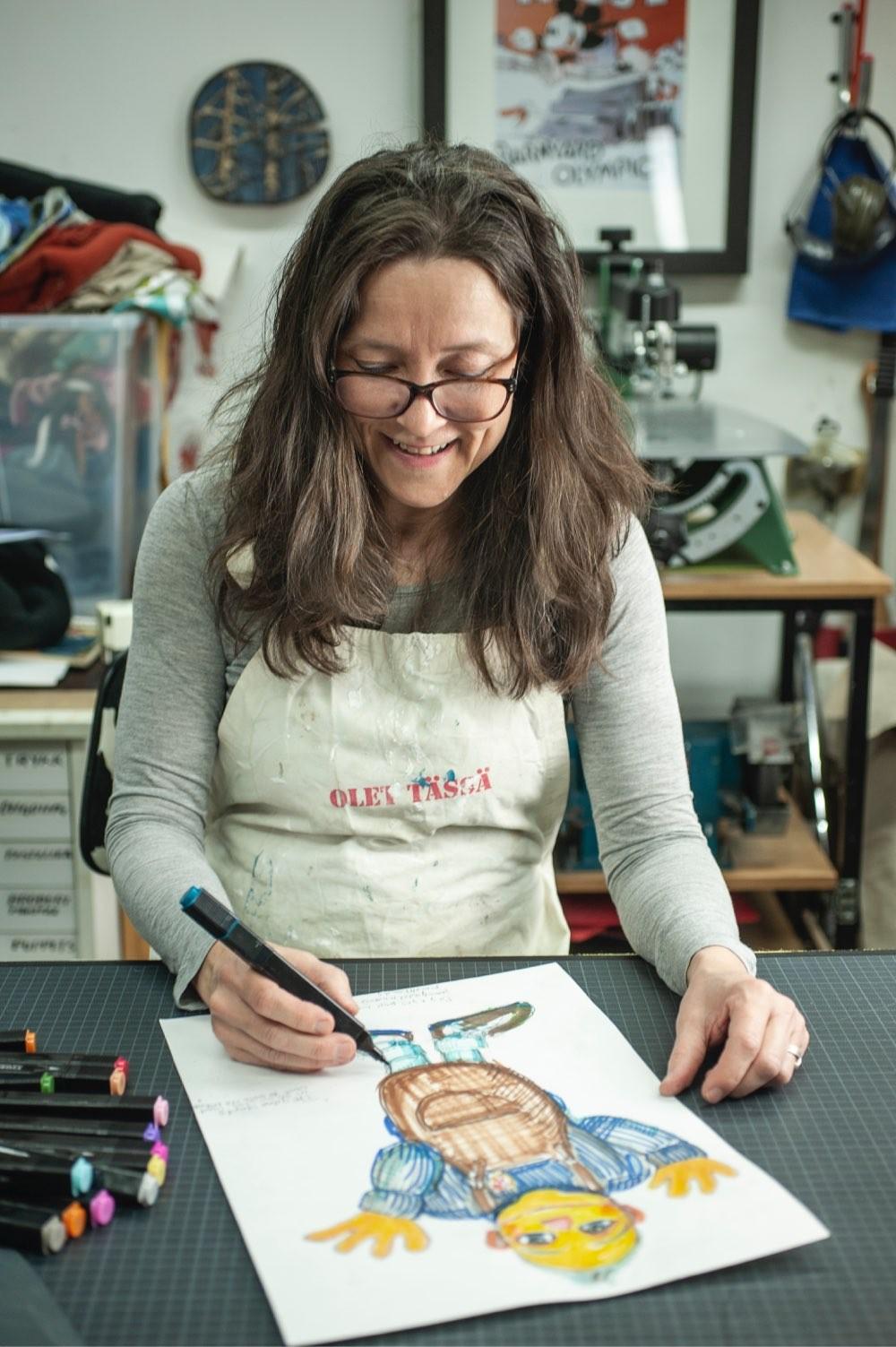 Tiina tegner en dukkefigur på papir
