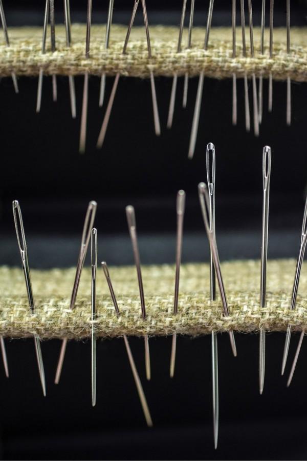 Ulike nåler stukket gjennom en hylle
