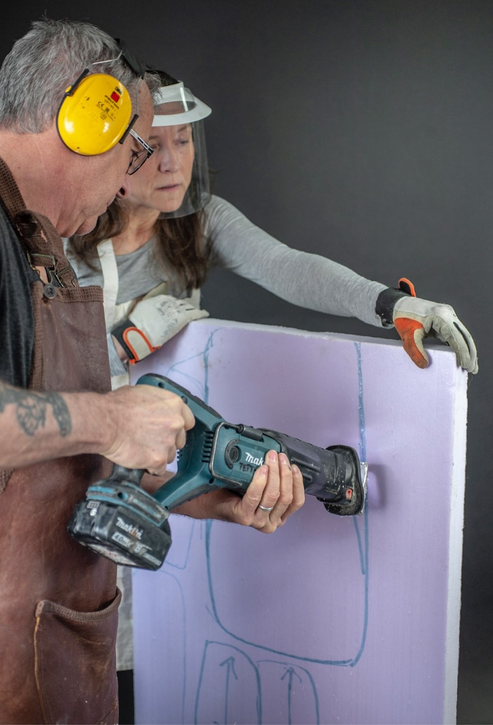 Tiina holds a foam plate while Sean uses an electric saw