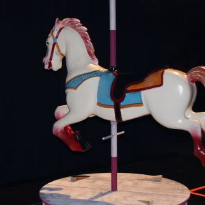 A profile of a white tivoli-horse with red feet and blue saddle