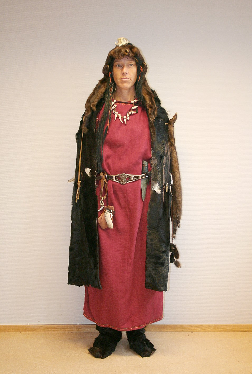 The Seeress woman in a long red Bronze Age dress, fur cape and decorated headpiece