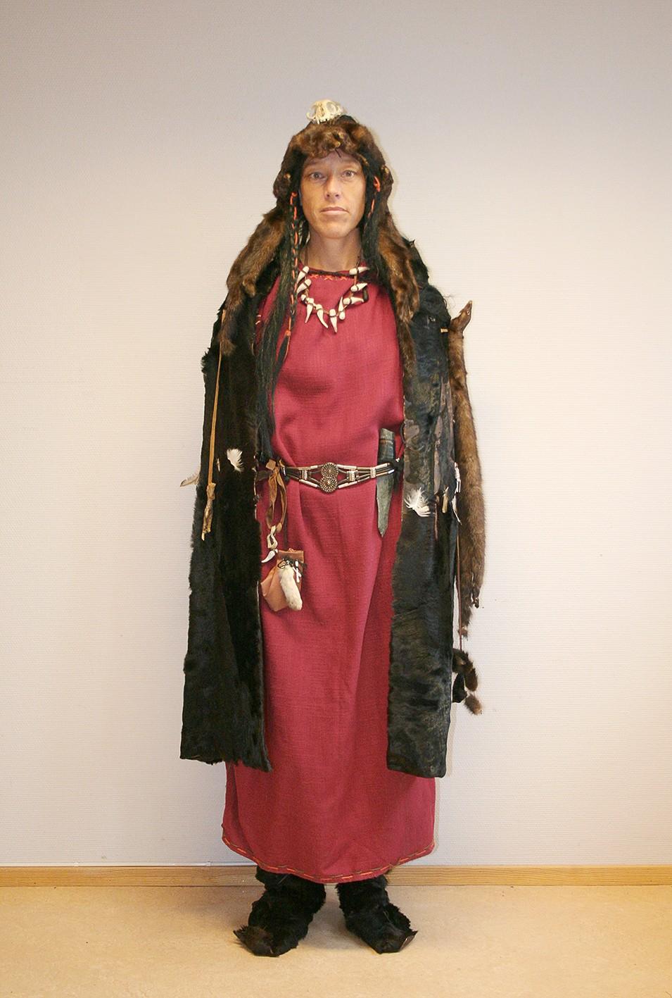 Volven i en lang rød bronsealderskjole, pelskappe og hodeplagg