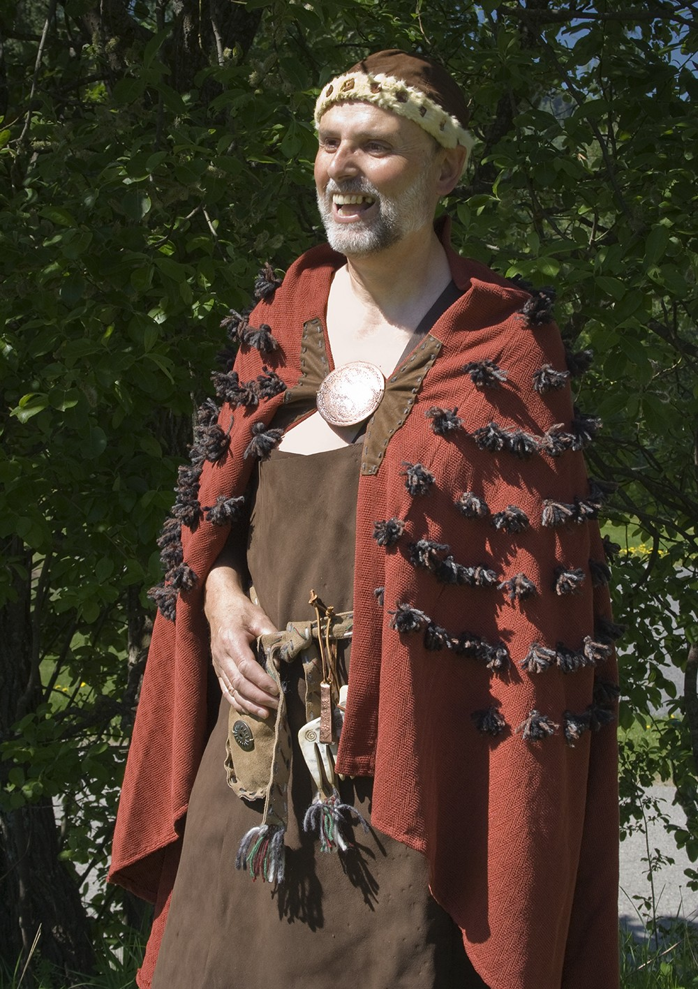 A man in a Bronze Age costume with a red furry cape and hat
