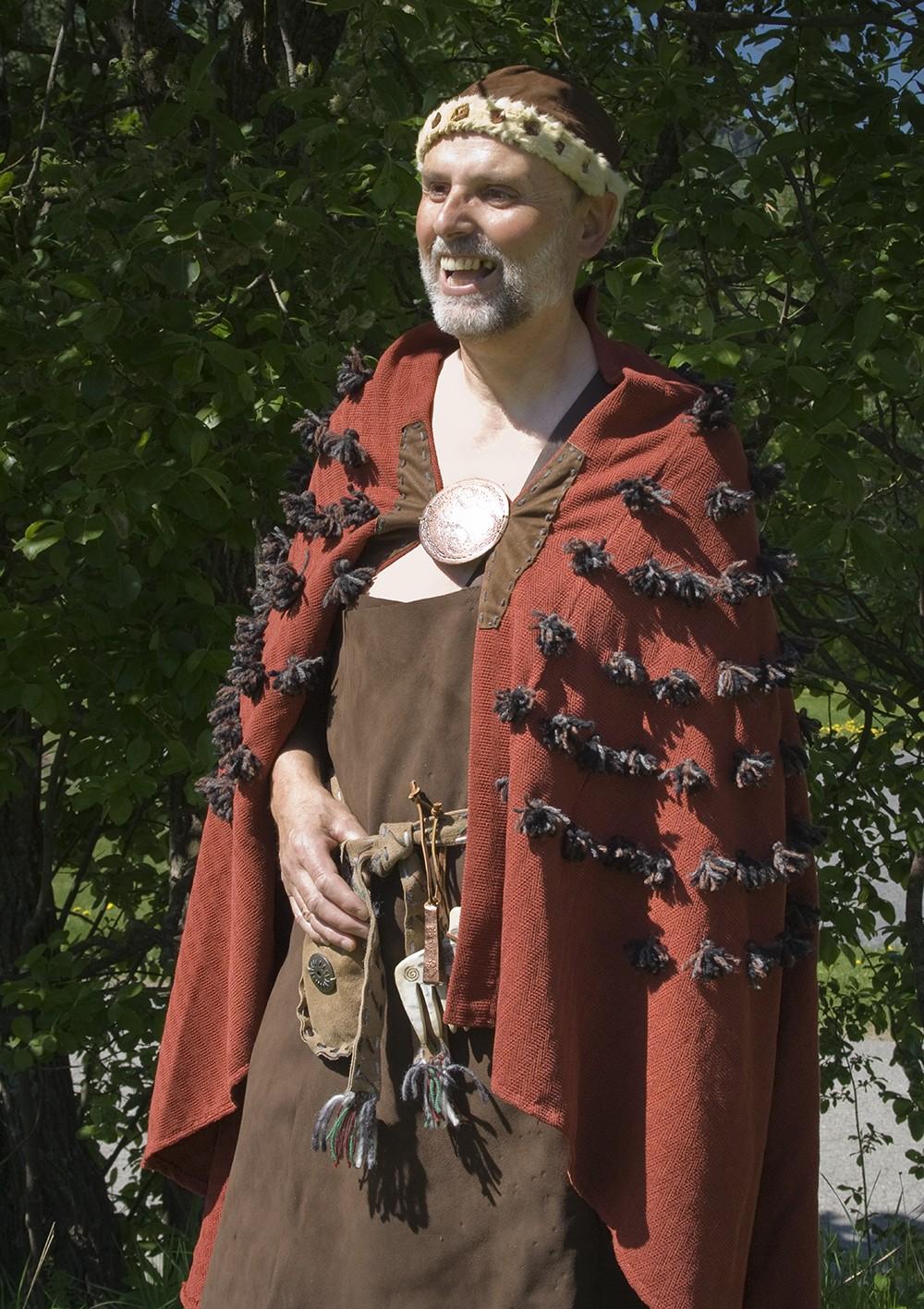 En mann i bronsealderkostyme med rød lodden kappe og hatt