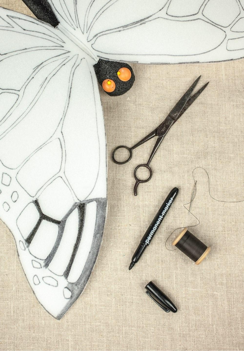 Saks, en penn og tråd, og sommerfuglvinger laget av en skumplate
