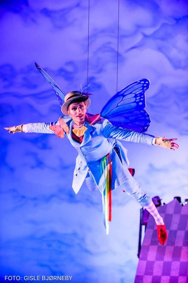 En sommerfugl spilt av en skuespiller i et blått kostyme og gul hatt