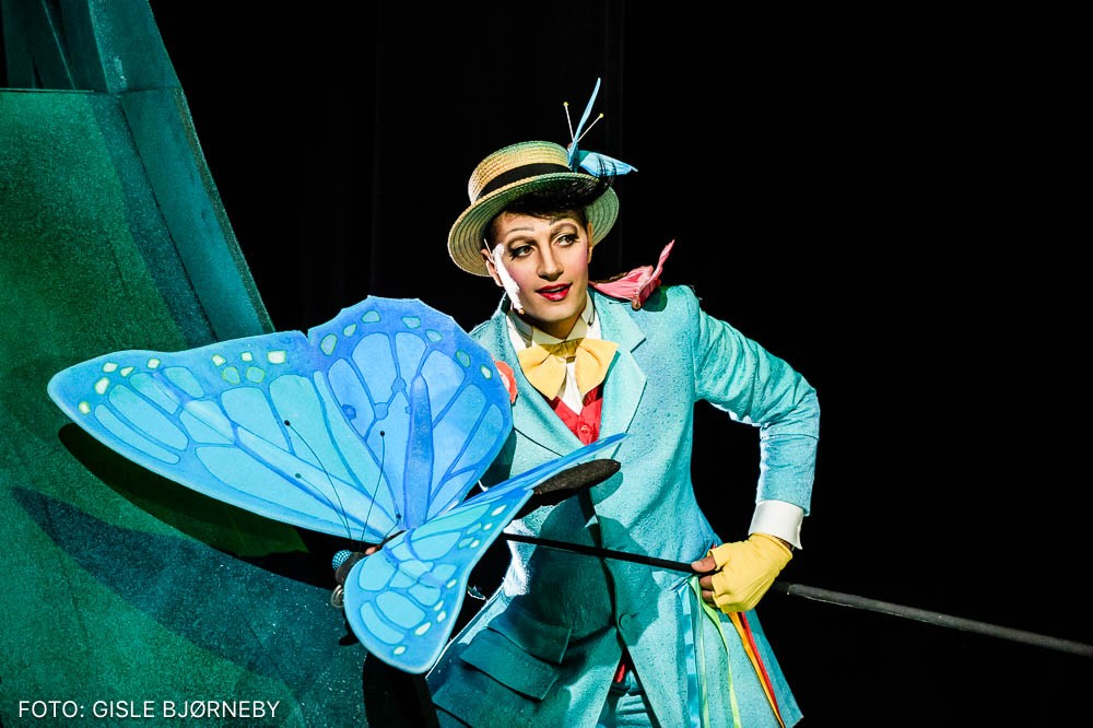 An actor in a blue costume and yellow hat holding a large butterfly fixed on a rod