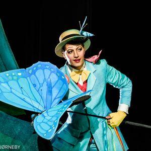 En skuespiller i et blått kostyme og gul hatt som holder en stor sommerfugl festet på en stang