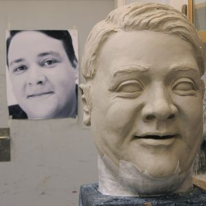 A big head is being modelled and casted. There is a enlarged photograph of the actor in the background
