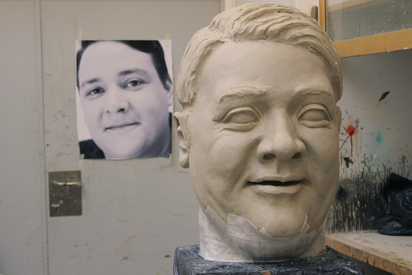 Et stort hode blir modellert og støpt. Et forstørret fotografi av skuespilleren finnes i bakgrunnen