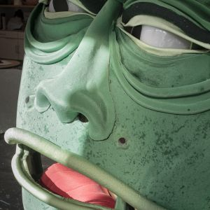 A close up portrait of a green big monster head