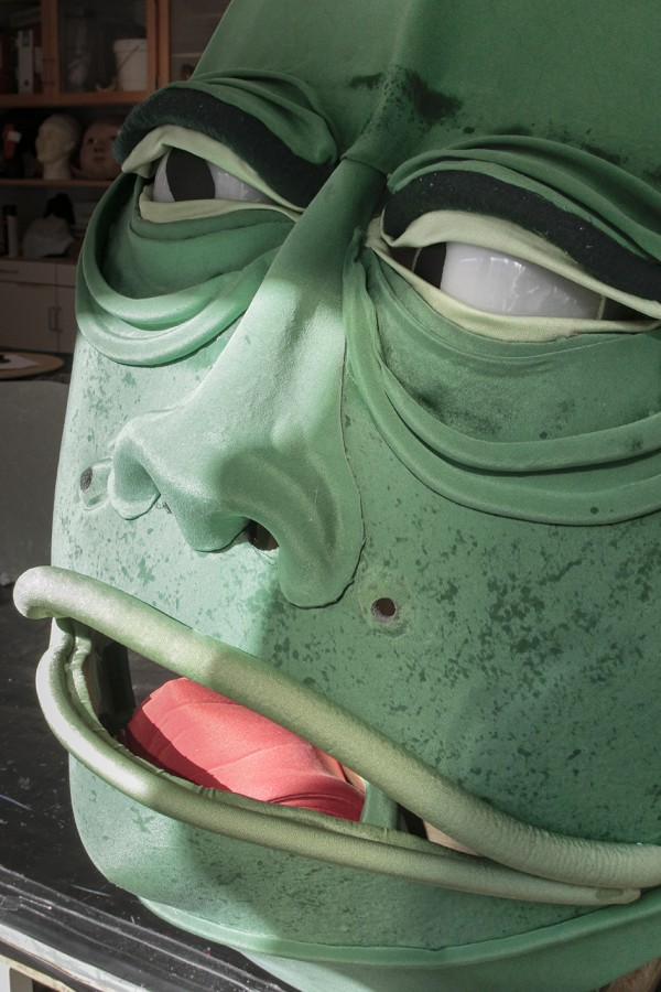 A close up portrait of a green big monster head