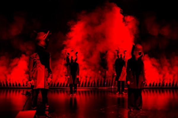 Skuespillere med neshornmasker står på en scene fylt med rødt lys og røyk