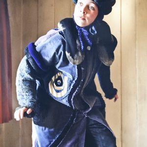 En skuespillerinne iført kostymet inkludert en blå spiss hatt og en blå, dekorert kåpe
