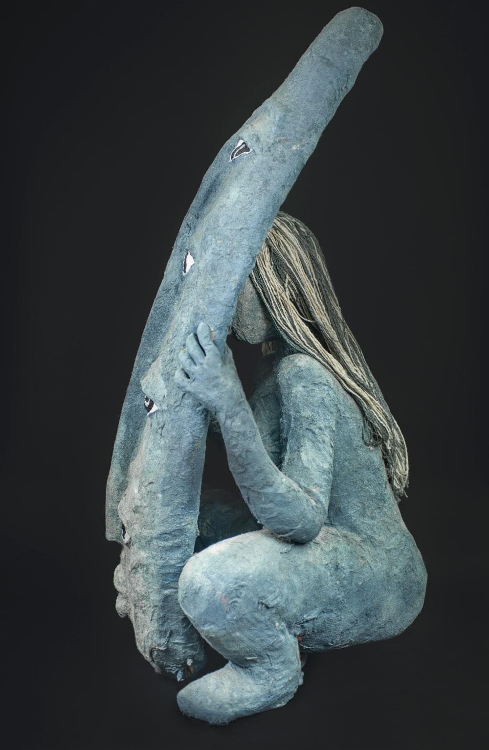 En grå kvinneskikkelse gjemmer seg bak et grått skjold med fire par øyne, sett fra siden