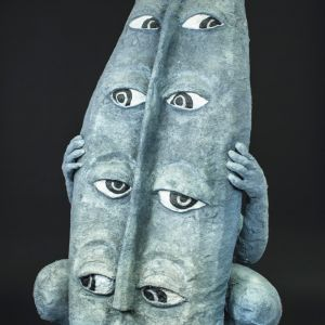 En face, a grey female figure hiding behind a grey shield with four pairs of eyes