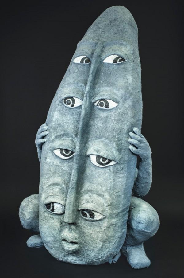 En grå kvinneskikkelse gjemmer seg bak et grått skjold med fire par øyne, sett forfra