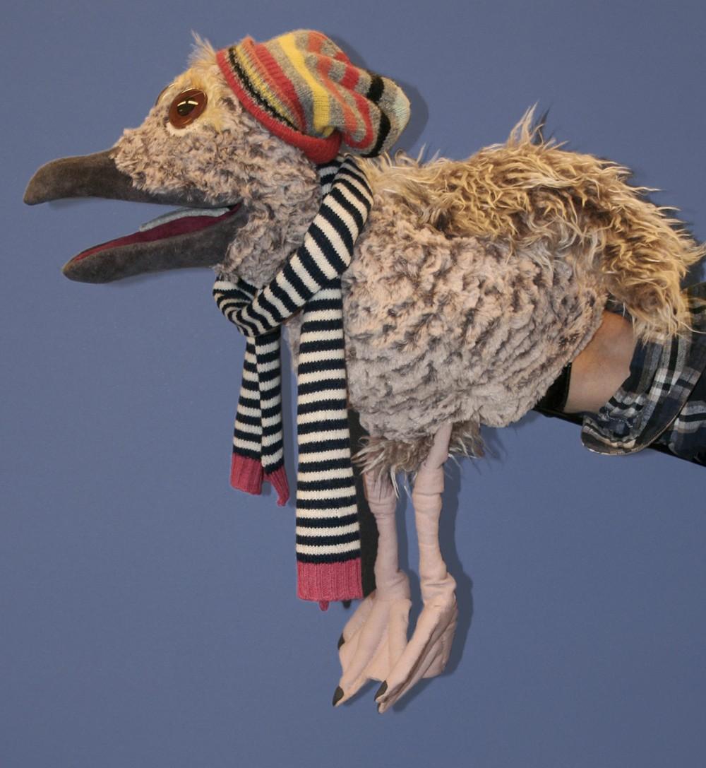 Et profilbilde av måke-dukken iført stripete skjerf og hatt