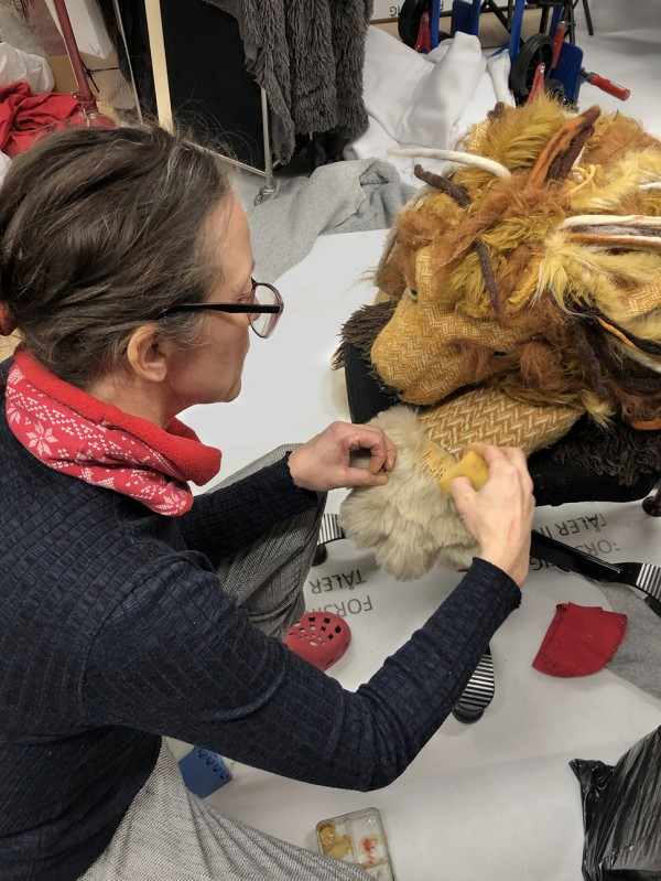 The lion puppet paws are being coloured.