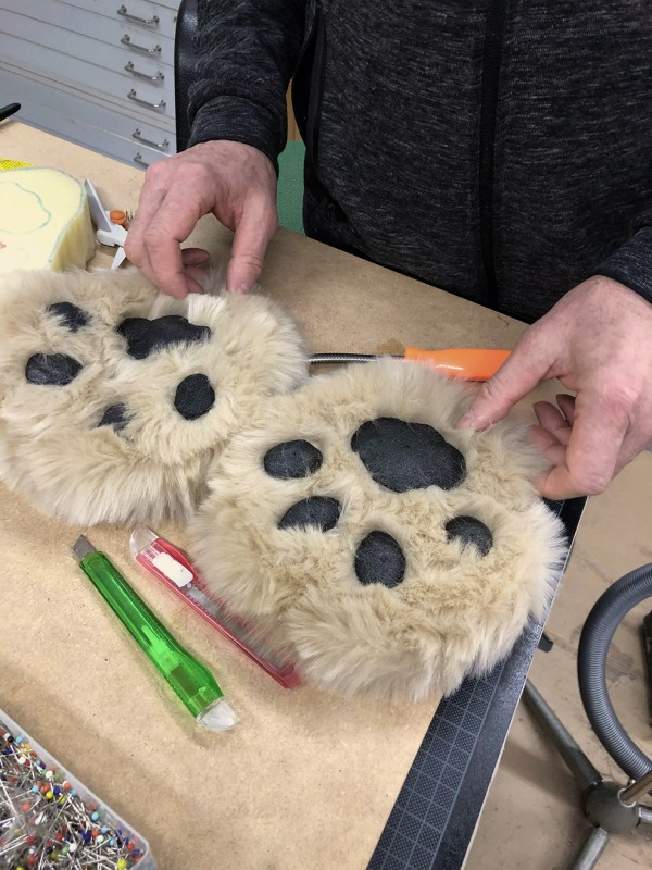 Lion puppet paws on the table.