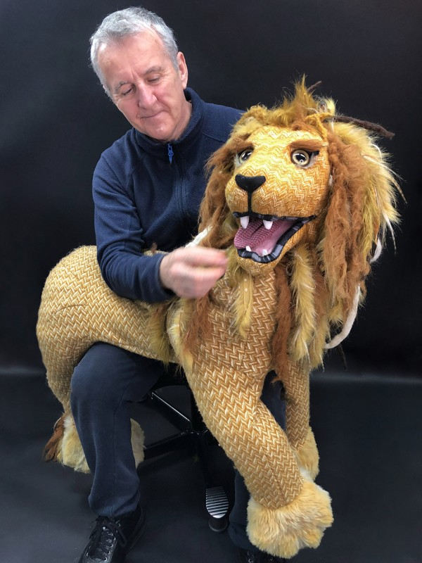 Sean with a lion puppet on his lap.